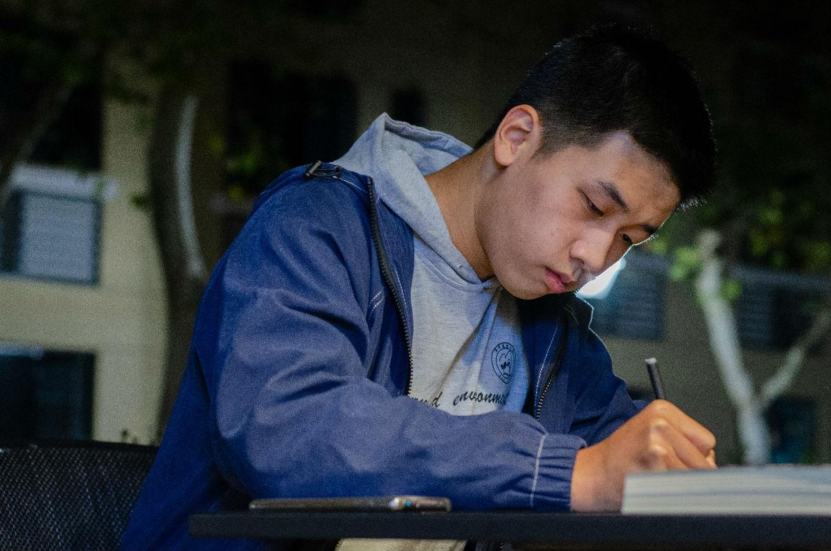 大学生标兵谢天正在给文字记者写下专业名词(学通社记者 汤景颢 摄)