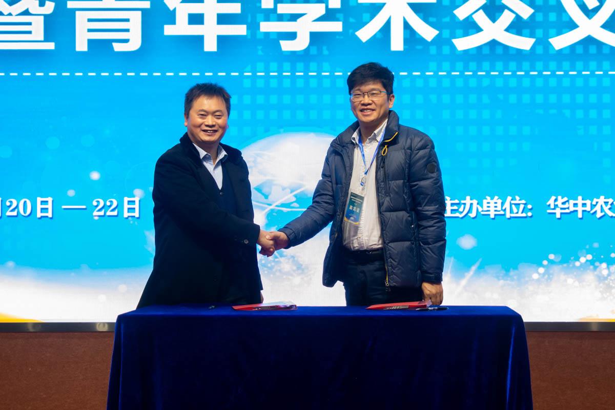 研讨会开幕式签约代表握手(学通社记者 邓颖骏 摄)