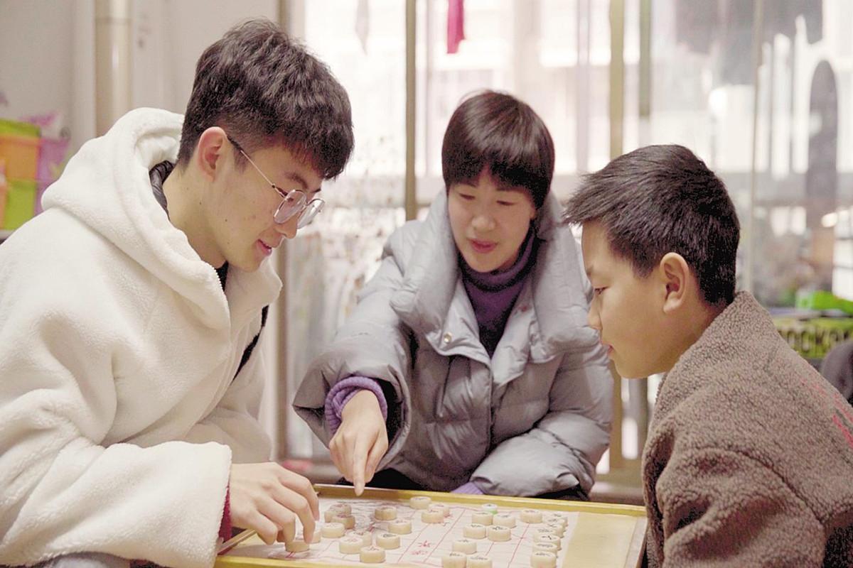 褚润泽(左一)和陈老师及其儿子下象棋。 (湖北日报全媒记者 龙华 胡雯洁 摄)