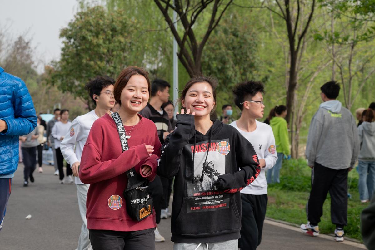 两名女生微笑着跑过沿湖东路(学通社记者 王晗藓 摄)_副本
