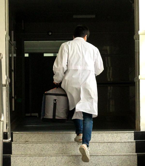 为了保证疫苗的及时供应,张伟医生都是小跑着运输疫苗(学通社记者 蔡雯雯 摄)