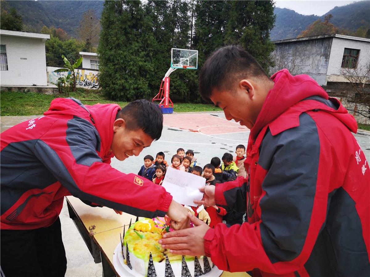 """""""本禹志愿服务队""""队员王庆鲁(右)与队友为贵州华农大石希望小学的留守儿童集体过生日。(本人供图)"""