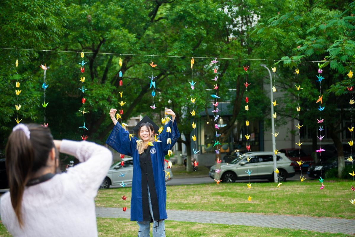 一位毕业生在千纸鹤阵前拍照留念(学通社记者 张鑫琪摄)