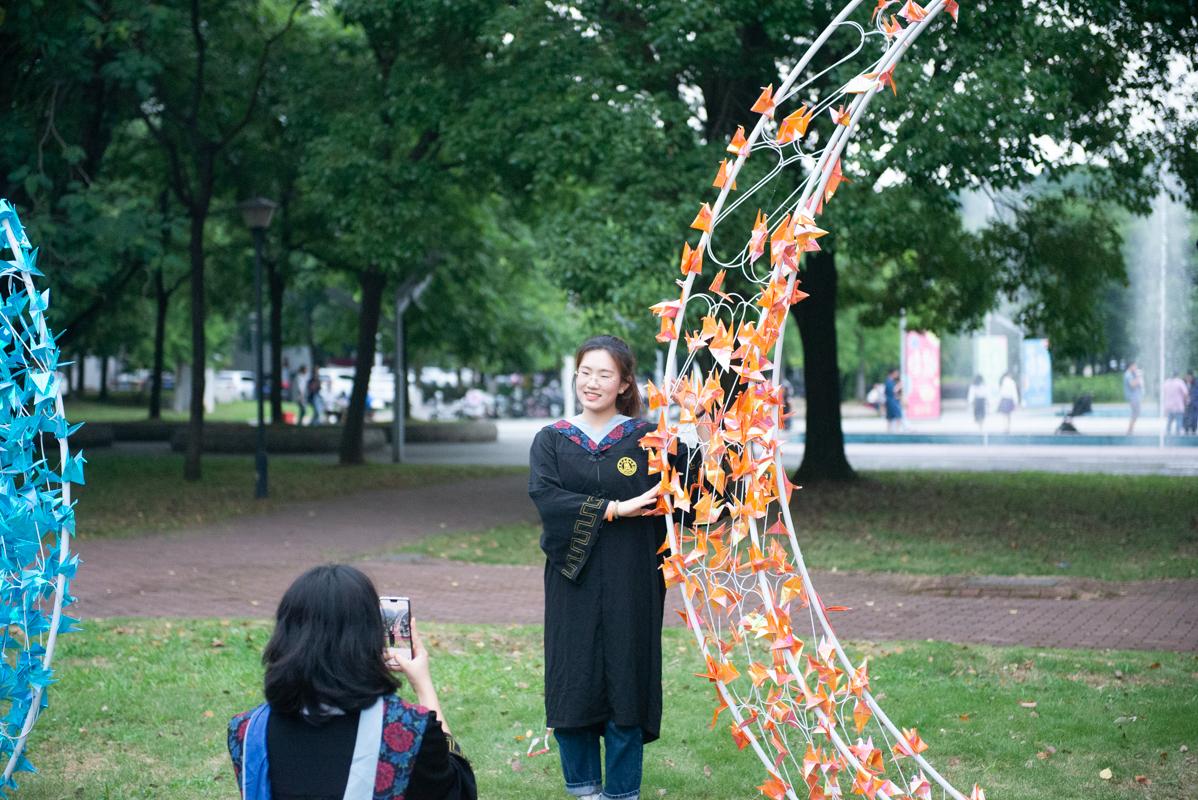 毕业生在布满千纸鹤的柱子前拍照留念(学通社记者 张鑫琪摄)