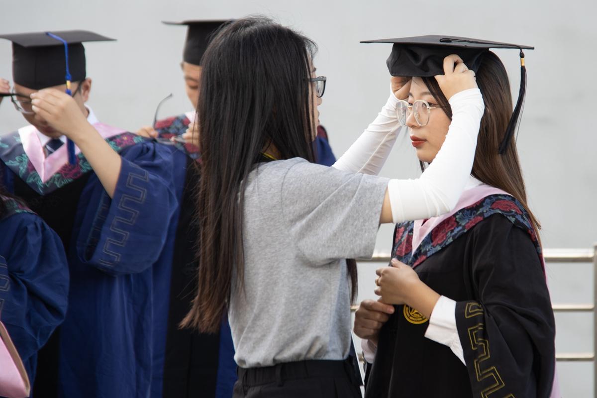 合影现场的工作人员为毕业生调整帽子(学通社记者 侯稼彤 摄)