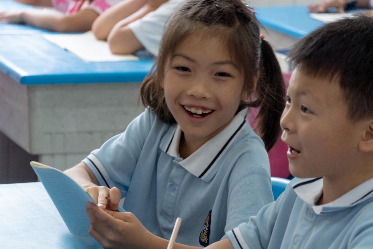 同学高兴地向同桌分享自己写的字(学通社记者 孔繁霄 摄)