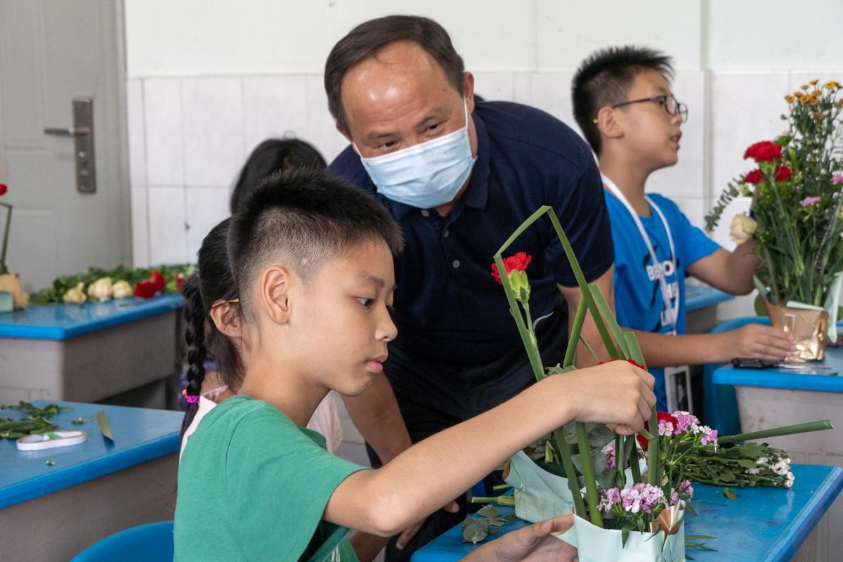 王建鸿询问附校暑期成长营7班同学的插花技巧学习情况(学通社记者 孔繁霄 摄)