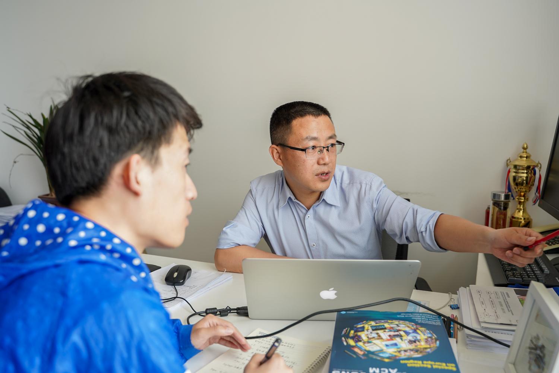 李国亮老师与学生探讨问题【学通社记者 孙泊远 摄】